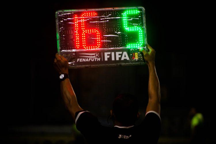 árbitros en el terreno de juego en la sustitución de equipos